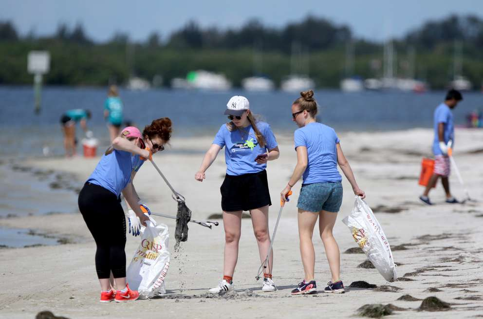From left, Katie Hogge, Jordana Merran, Maddie Black and Katie Morgan, with the Ocean Conservancy, collect a plastic trash bag which was buried in sand at a beach on the South Gandy Channel in Tampa Bay during a coastal cleanup event on June 26 in St. Petersburg. (DOUGLAS R. CLIFFORD | Times)