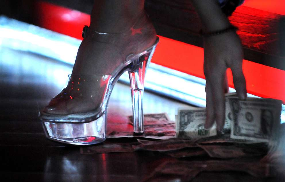 A dancer collects her tips from the stage floor at Mons Venus gentleman's club. (Times 2012)