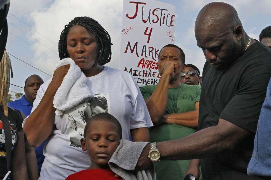 Michael McGlockton, the father of Markeis McGlockton, wipes the face of his grandson, 5-year-old Markeis McGlockton Jr., during a rally July 22. LUIS SANTANA   Times