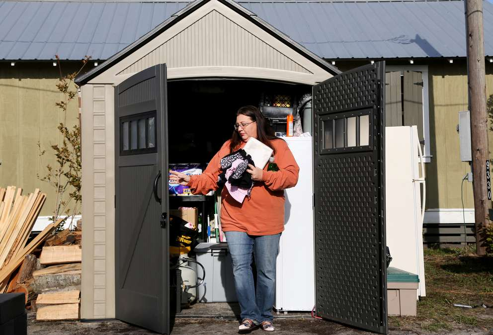 Laurie June collects supplies Dec. 12 from a storage shed near her 24-foot camper where she lives with her husband, three dogs and two cats in Mexico Beach. June and her family were displaced from their home as a result of damage caused by Hurricane Michael which made landfall two months ago. (DOUGLAS R. CLIFFORD | Times)