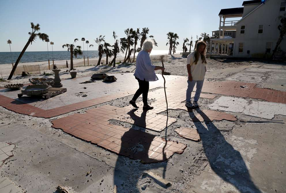 Peggy Wood, left, and her daughter Shawna Wood walk on the slab where the Driftwood Inn once stood in Mexico Beach. (DOUGLAS R. CLIFFORD | Times)