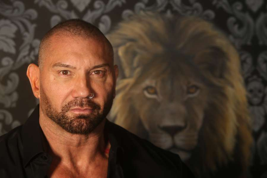 Dave Bautista poses at his Tampa office with a painting by Meaghan Farrell  Scalise.