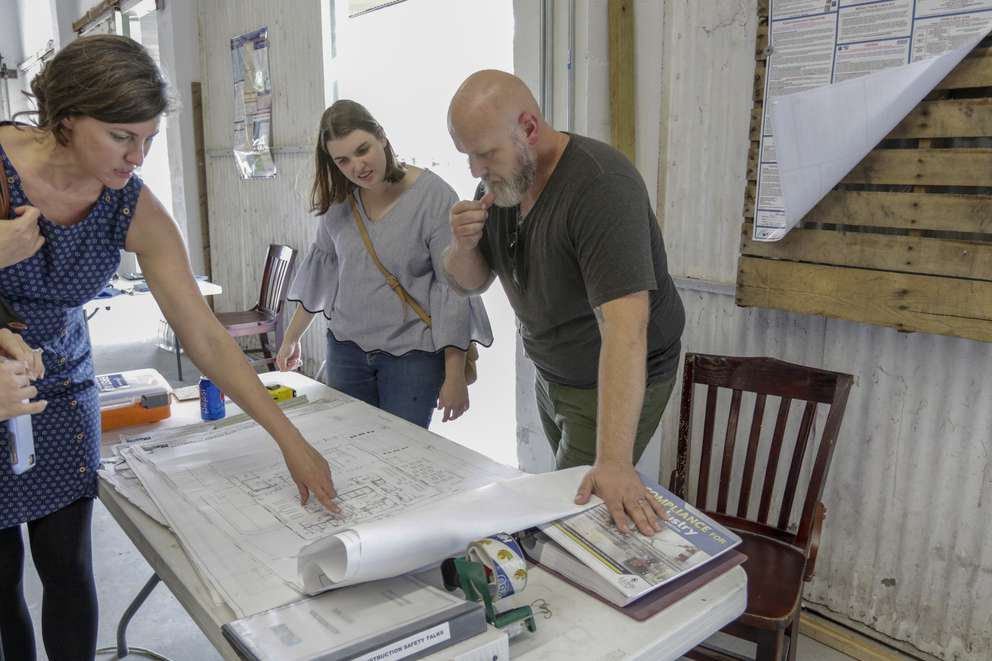 John and Sarah Buckley (left) with Catapult kitchen director, Maggie Leach (center) look over plans for The Joinery, a food hall space coming to Lakeland. [MARTHA ASENCIO-RHINE   Times]