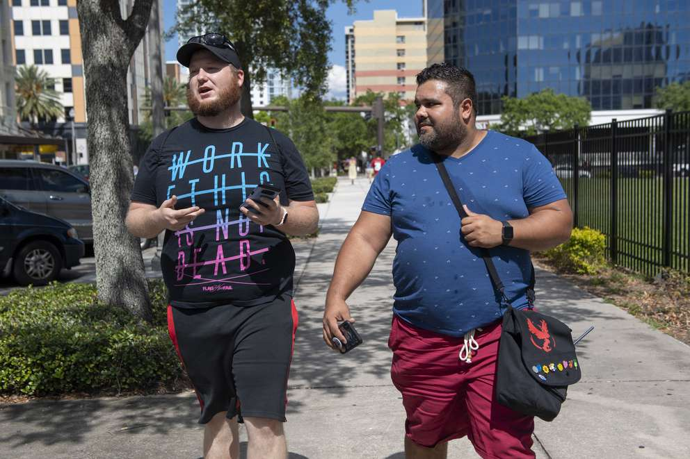 Josh Smolko, 27, from Lakewood Ranch and Noah Diaz, 31, from St. Petersburg, play Pokemon Go while walking down Central Avenue on Sunday, May 19, 2019 in St. Petersburg. Diaz's bag clearly showed he was on team Valor. It had a symbol of the team, as well as pins for the different types of Pokemon. ALLIE GOULDING | Times