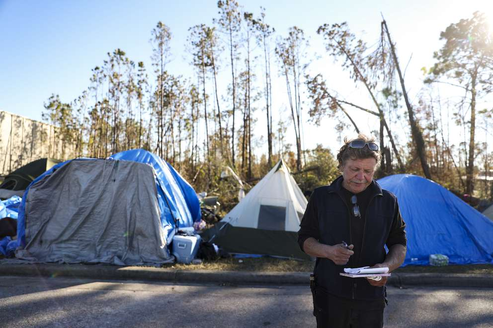Jim Reno, an unofficial camp leader, walks through a tent city that sprang up after Hurricane Michael hit Panama City. Those sleeping in the tents at Forest Park United Methodist Church included out-of-town workers and local residents with nowhere else to go. The tents are now gone. [MONICA HERNDON | Times]