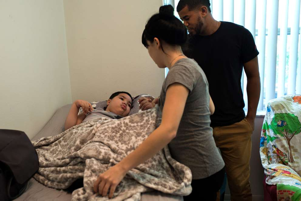 Karen Maldonado and John Viera put their son, Jean Kariel, to bed. He had a stroke after a heart transplant at All Children's last year. His parents care for him full time. [NEIL BEDI | Times]