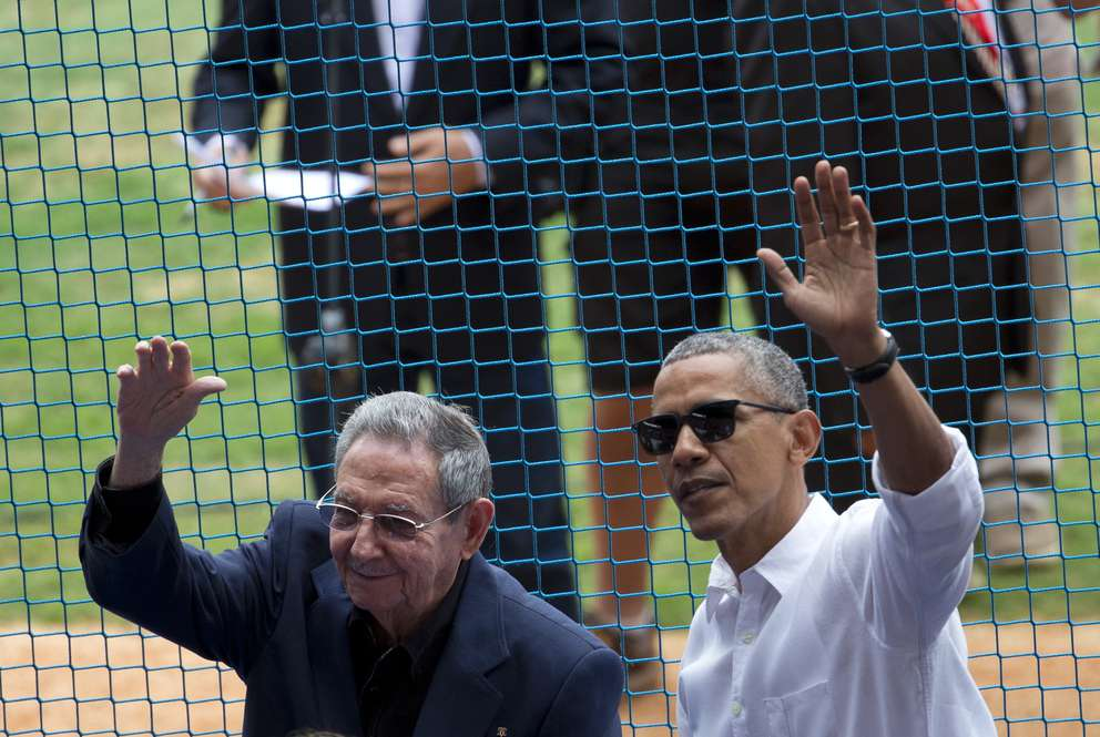 This March 22, 2016 photo shows U.S. President Barack Obama, right, and his Cuban counterpart Raul Castro wave to cheering fans as they arrive for a baseball game between the Tampa Bay Rays and the Cuban national baseball team, in Havana, Cuba. [AP Photo/Rebecca Blackwell]