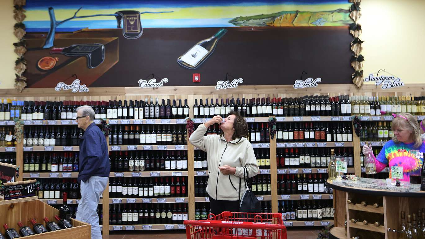 Trader Joe's customers sampled wines during the opening of the new St. Petersburg store, Friday February 13, 2015 under a store mural showing a wine bottle imitation of artist Salvador Dali's painting, The Persistence of Memory. The store is decorated with various St. Petersburg themed murals. [SCOTT KEELER | TIMES]
