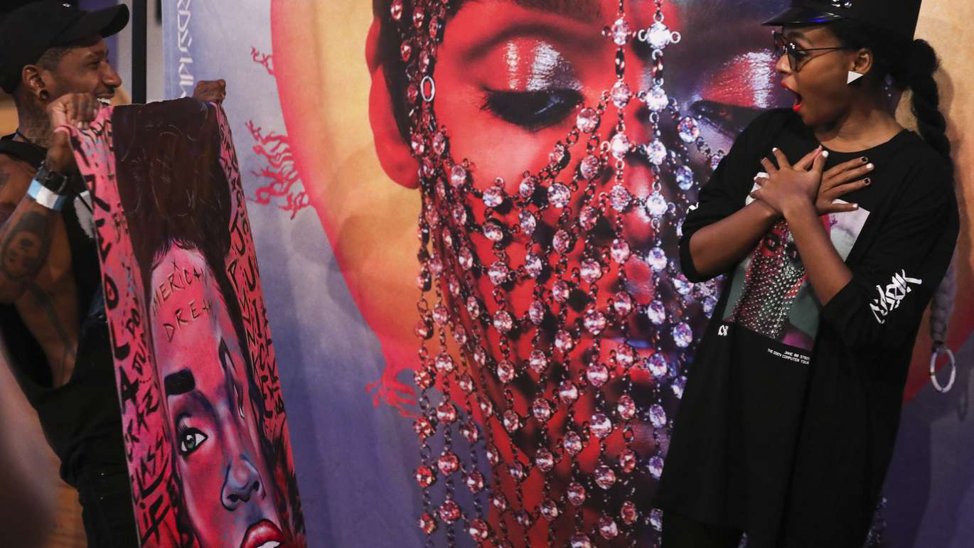 Tampa artist Cam Parker gives his painting to musician Janelle Mon‡e after her performance at Jannus Live on Thursday, July 26, 2018. Parker also made a mural for musician Lady Gaga in Tampa. [EVE EDELHEIT   Times]