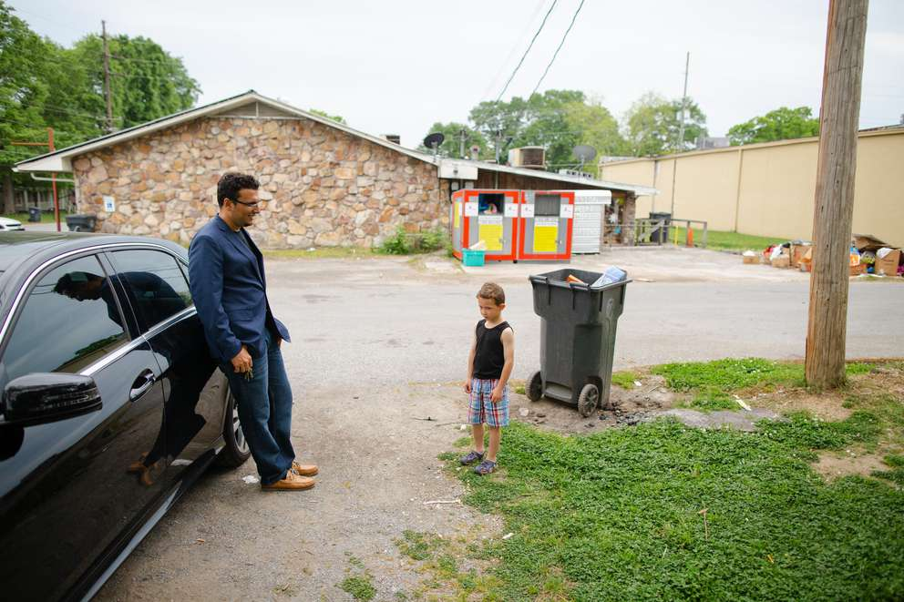 Heval Kelli leans against his sedan as he chats with C.J. Buckley, who at age 4 attended a Klan rally with his father. [Photo for The Washington Post by Kevin D. Liles]