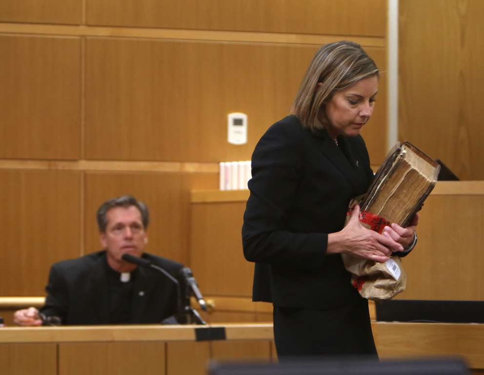 Assistant Public Defender Jane McNeill removes John Jonchuck's Bible after showing it to Fr. Bill Swengros. [SCOTT KEELER | Times]