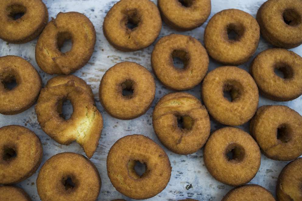 Doughnuts cool on the rack after being fried in the kitchen at Dough. (Times, 2016)