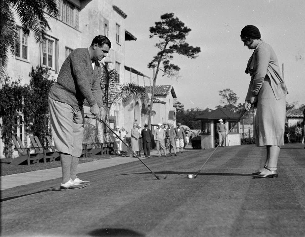 Babe Ruth shows his daughter Julia Ruth how to swing on the golf course at St. Petersburg on Feb. 11, 1931. [AP Photo]