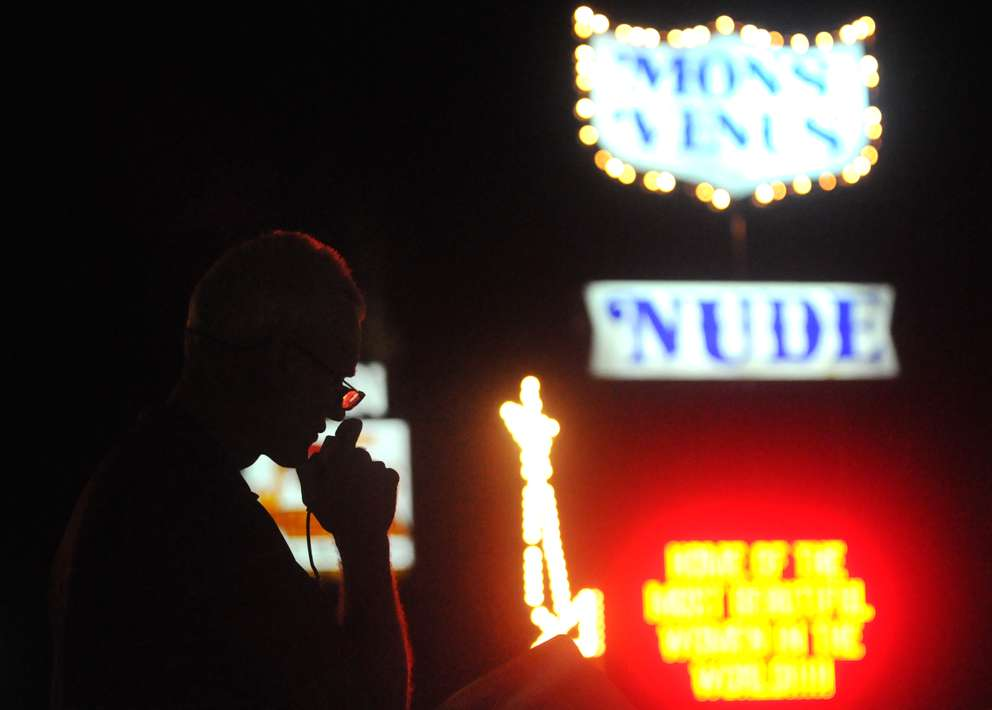 Evan Johnston reads from a devotional book into a megaphone outside of Mons Venus gentleman's club in Tampa, FL. Times (2012)