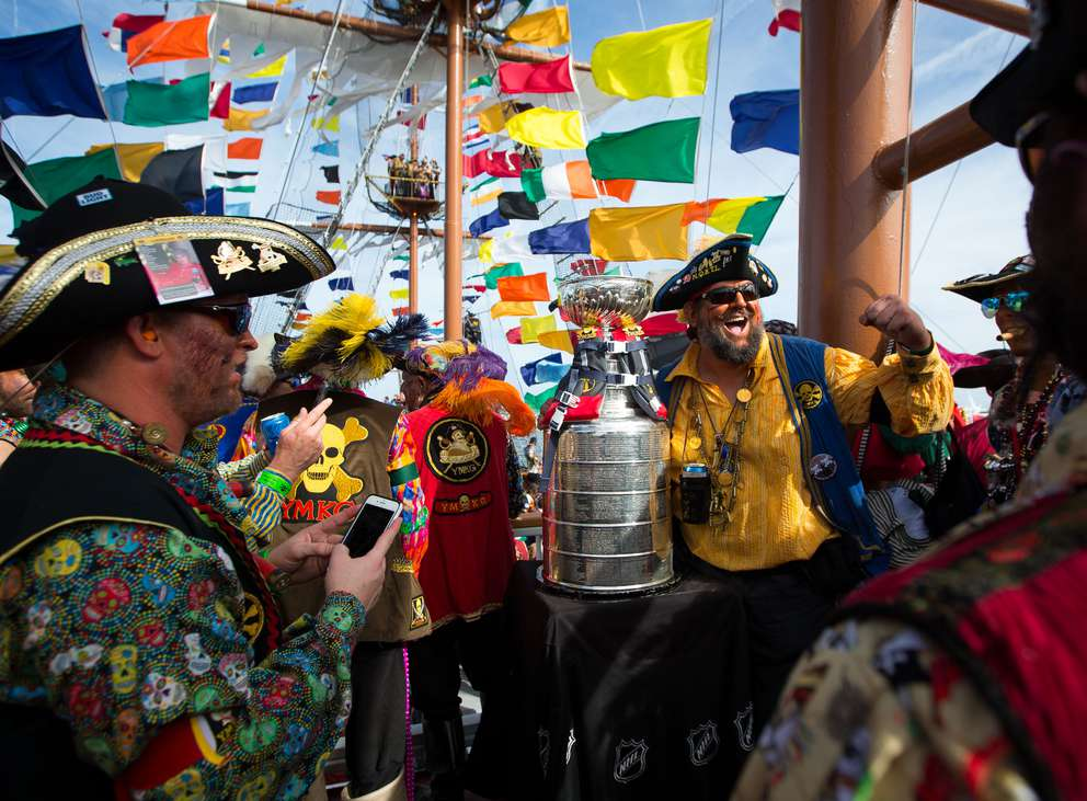 Ye Mystic Krewe of Gasparilla members crowd around the NHL Stanley Cup aboard the Jose Gasparilla pirate ship at the end of the Ballast Point Park pier on Jan. 27, 2018. The ship carried the cup for the annual invasion. [Loren Elliot | Times]