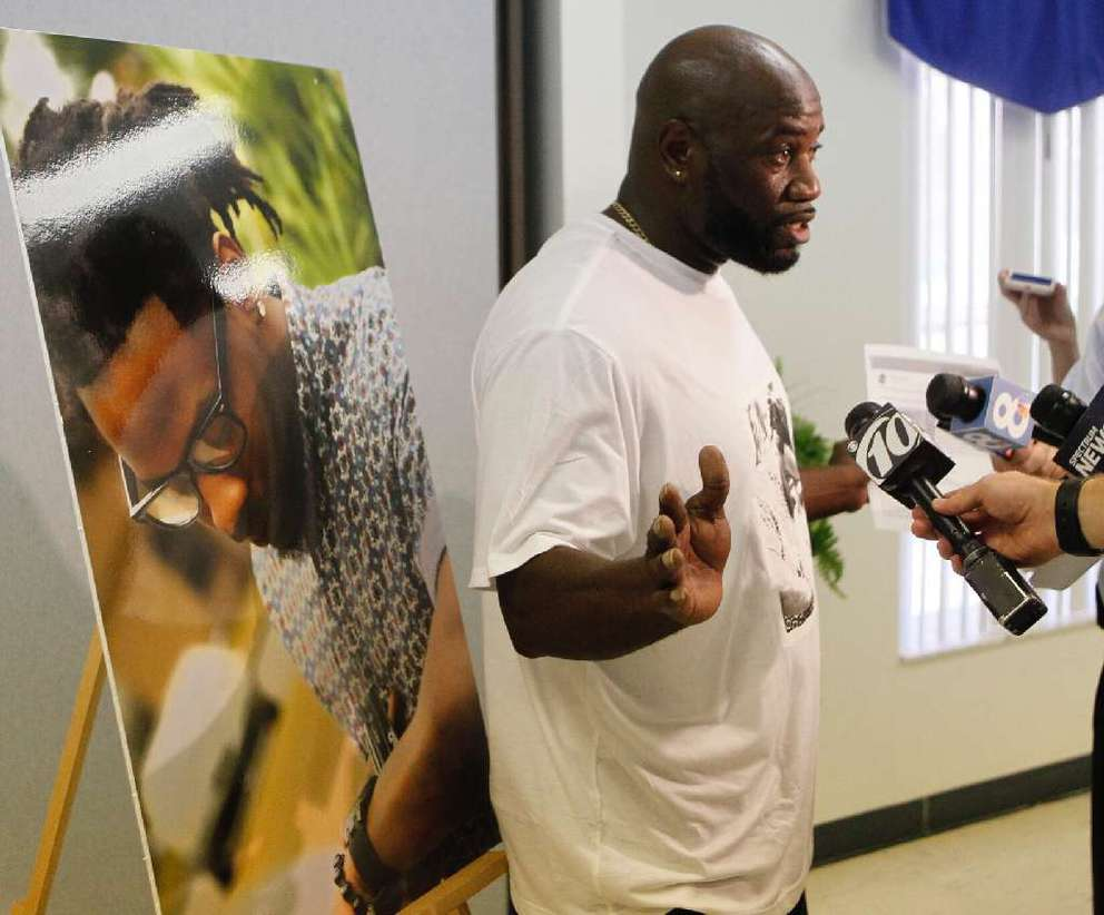 Michael McGlockton stands in front of a photo of his son, Markeis, during a news conference July 24. He says Markeis was backing up when he was shot. JIM DAMASKE | Times