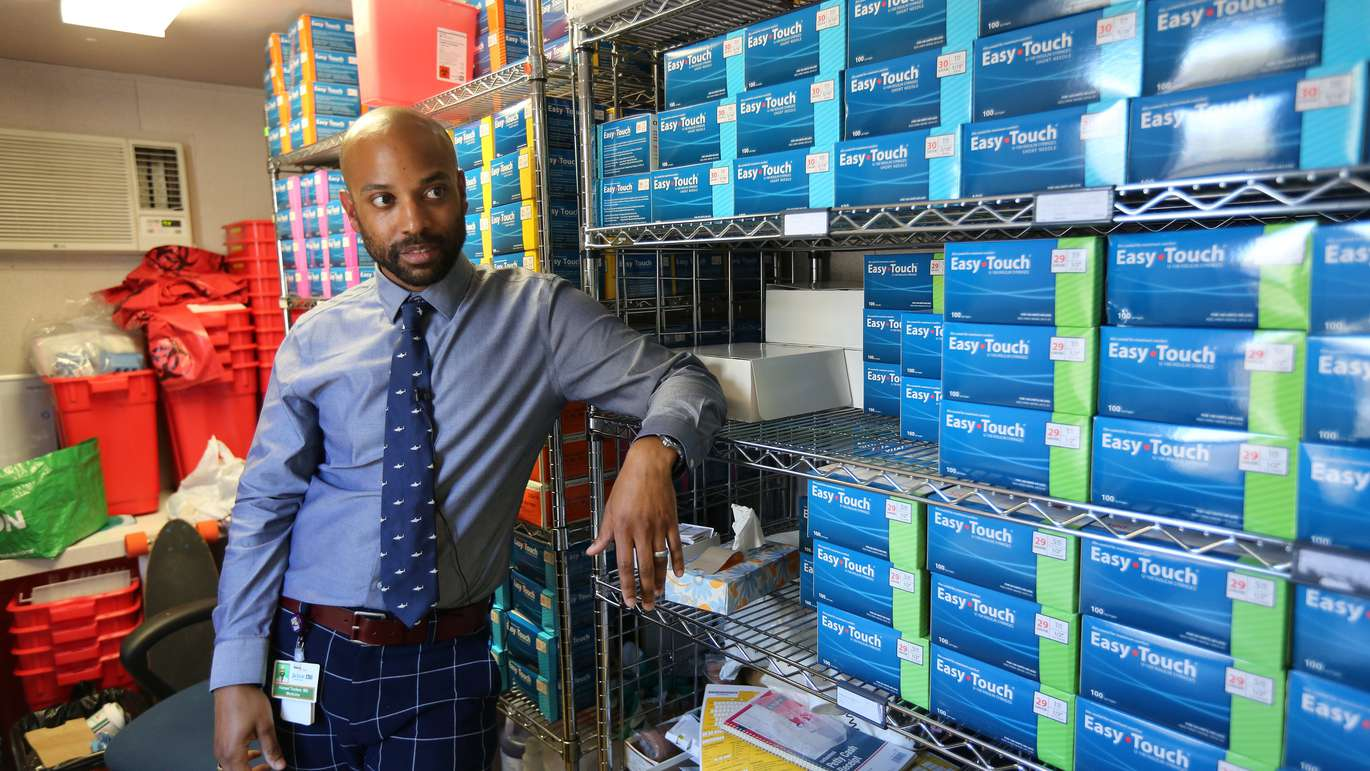 Dr, Hansel Tookes who fought for and started Miami's IDEA Needle Exchange, a UM program that provides addicts with clean needles to prevent transmission of disease and Narcan, a substance that reverses opioid overdoses, stands in the supply room Friday, February 15, 2019, surrounded by boxes of sterile needles. Emily Michot/Miami Herald