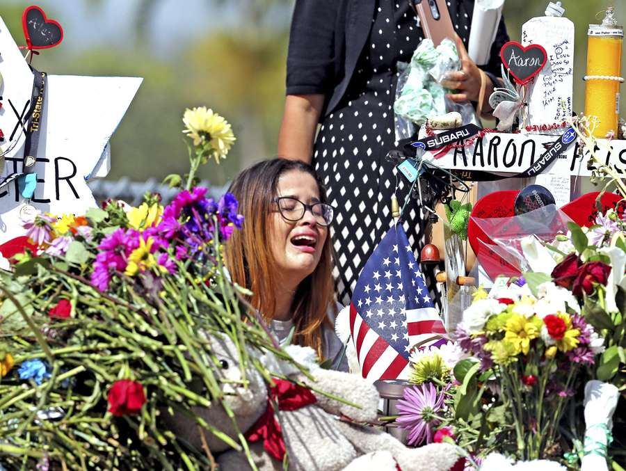 Marjory Stoneman Douglas High School former student Ariana Gonzalez weeps at a cross of slain Marjory Stoneman Douglas coach Aaron Feis, on a hill honoring those killed in Parkland. Over a dozen students and teachers were killed on Valentine's Day in a mass shooting at the high school. (Charles Trainor Jr./Miami Herald via AP)