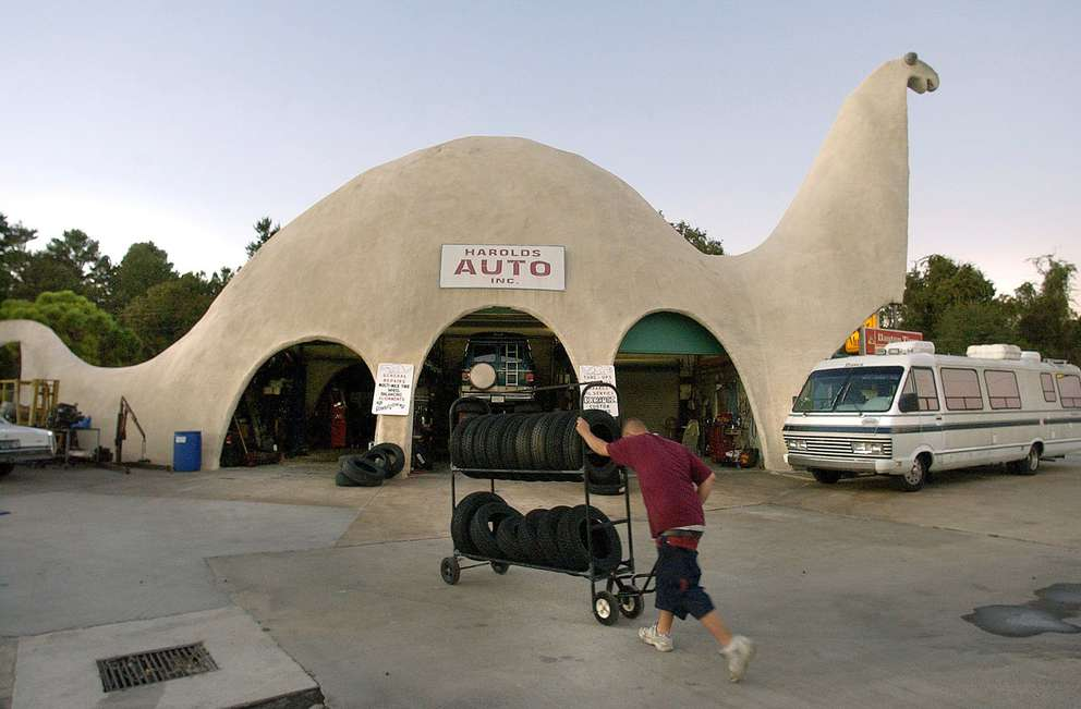 Christopher Rainey rolls tires into one of the bays at Harold's Auto Station the end of the day. The building is 47 feet tall and 110 feet long. Times (2003)