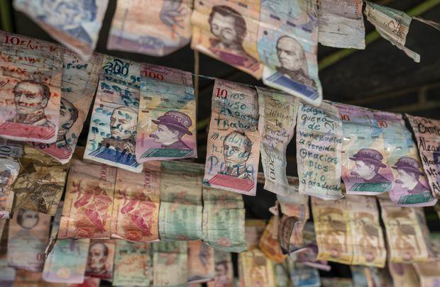 La moneda venezolana sin valor cuelga del techo en un kiosco en Cúcuta. donde los refugiados venezolanos, recientemente cruzados a Colombia, escriben notas para familiares, amigos o simplemente para compartir pensamientos antes de continuar su viaje.