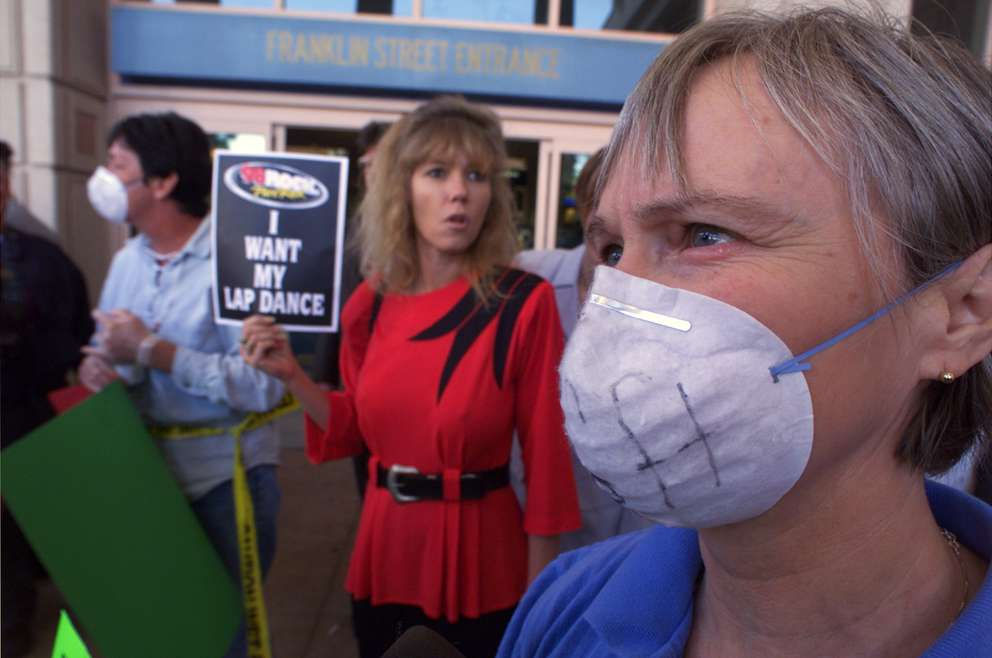 From left, dancer Kathy Hochholzer Chanda and Betty Lamb stand outside the Tampa Convention Center in support of lap dancing. They wore surgical gloves and mask as well as a 6-foot piece of crime scene tape to mock the proposed ordinance. Times (1999)