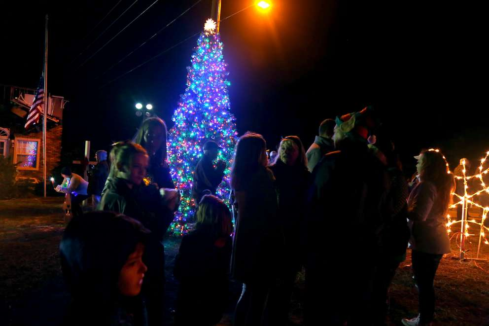 Residents of Mexico Beach visit during the annual Christmas tree lighting festival hosted on the lawn in front of Mango Marley's restaurant and the Parker Realty building on U.S. 98 in Mexico Beach. (DOUGLAS R. CLIFFORD | Times)
