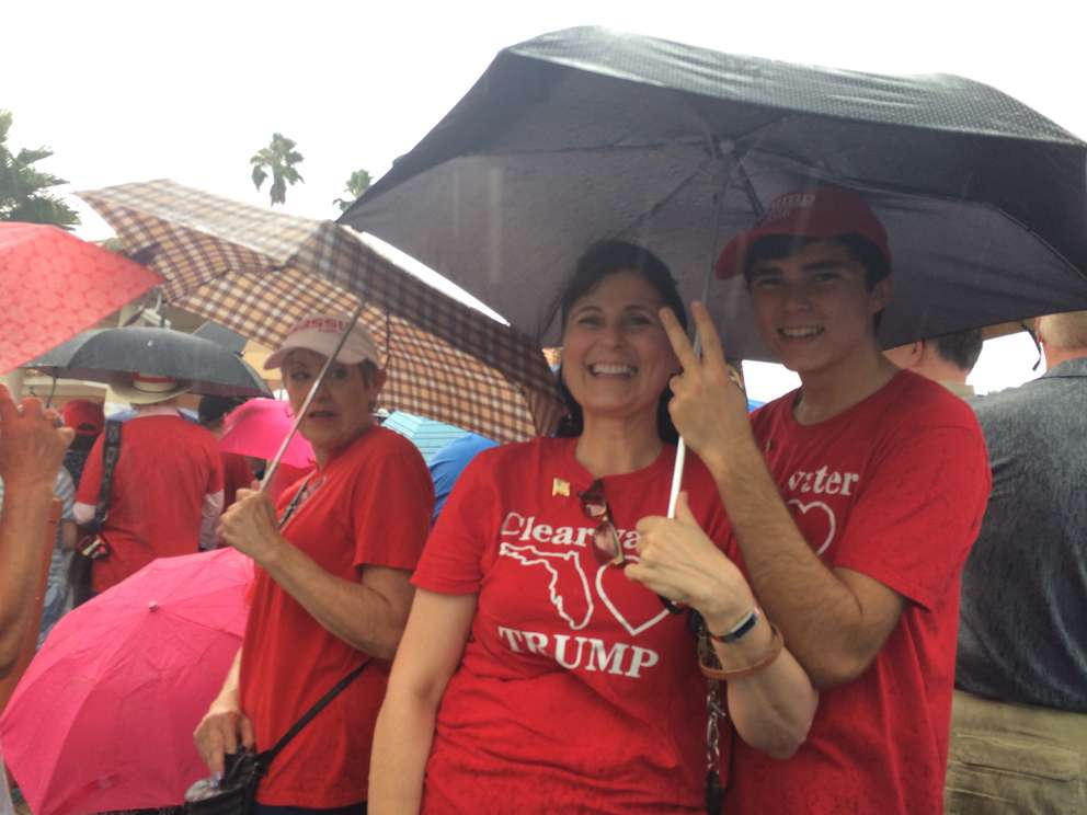 Shawn Float, left, and son Arden Taylor, right, from Clearwater huddle underneath an umbrella waiting for Trump to arrive in Tampa. [Tim Fanning | Times]