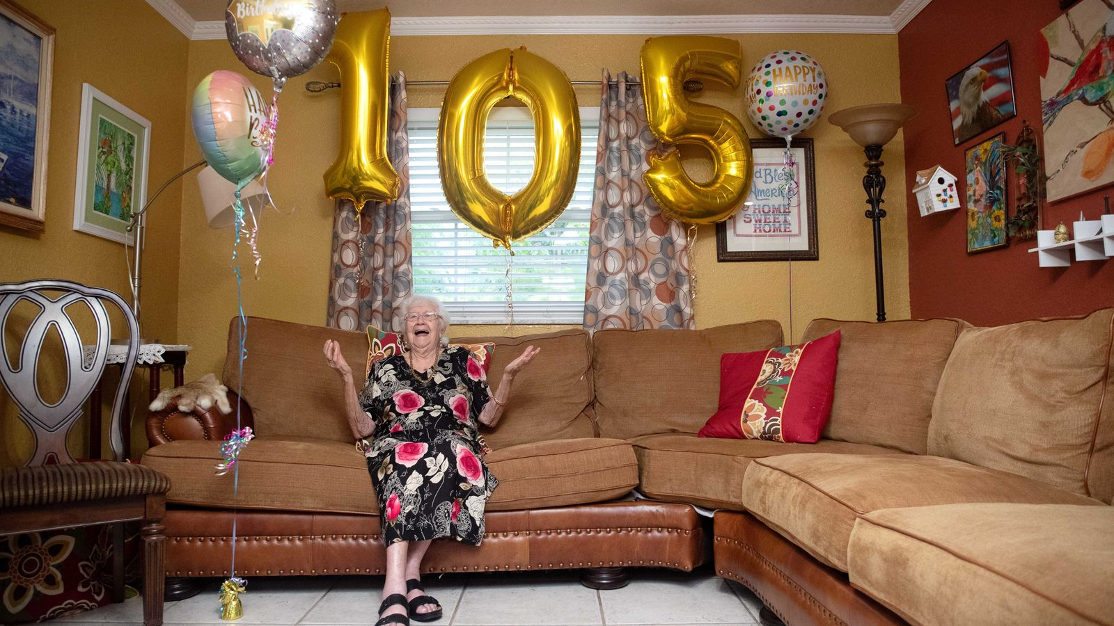 """Idelisa """"Yaya"""" Oliviera laughs beneath birthday balloons at her 105th birthday party on Aug. 14, 2021, in Tampa."""