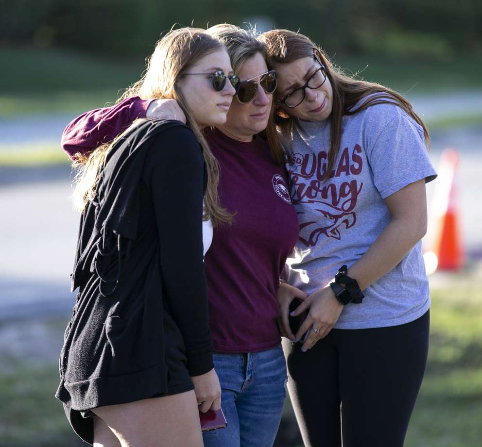 Emma Rothenberg, 20, with her mother Cheryl Rothenberg and sister, MSD student, Sophia Rothenberg, 17, embrace at the memorial at the school during one-year anniversary of the shooting death of 17 at Marjory Stoneman Douglas High School in Parkland, Fl. on Thursday, Feb. 14, 2019. [Al Diaz | Miami Herald]