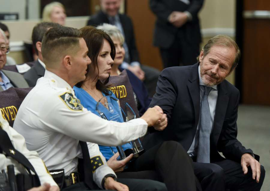 Sheriff Chad Chronister, left, congratulates his patron, former Sheriff David Gee, as Gee receives a good government award in April from the Hillsborough County Commission. Gee's wife Rhonda is at center. [CHRIS URSO | Times]