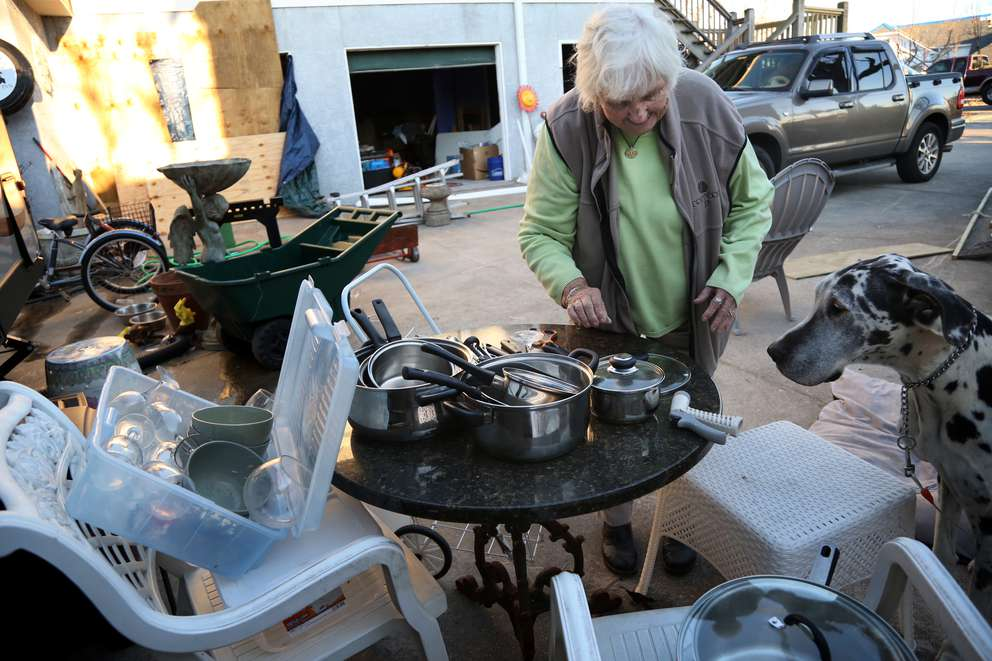 Peggy Wood visits with her Great Dane, Woodie, while sorting through a pile of pots and pans collected from the rubble of the Driftwood Inn. DOUGLAS R. CLIFFORD | Times