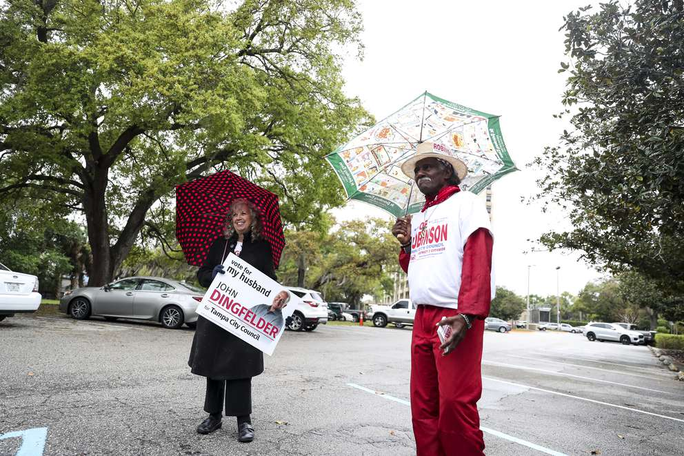 Lynn Dingfelder, wife of City Council District 3 candidate John Dingfelder, and Marvin Youngblood, campaign manager for District 2 candidate Joe Robinson, campaign in the rain on Tuesday at the voting precinct at Tampa Garden Club. [MONICA HERNDON | Times]