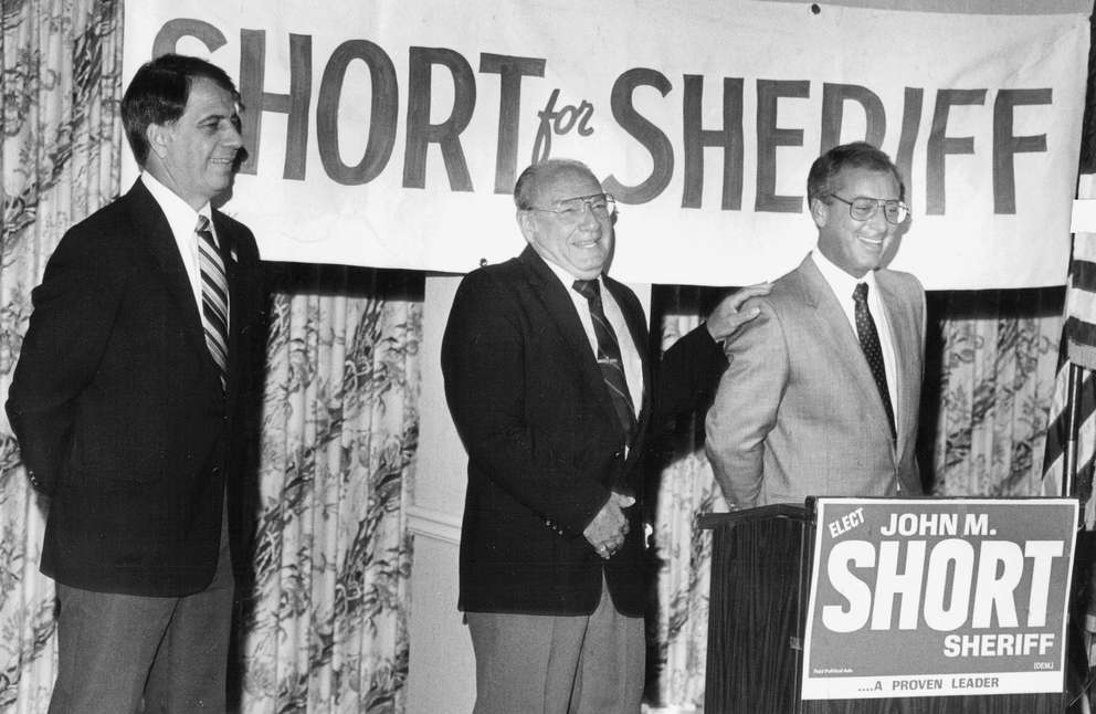 Left to right: Former Republican sheriff's candidate Manny Funes and former Democratic sheriff's candidate Sam Falzone lend their support to Democrat John Short in his 1984 bid for Pasco County Sheriff. Times (1984)