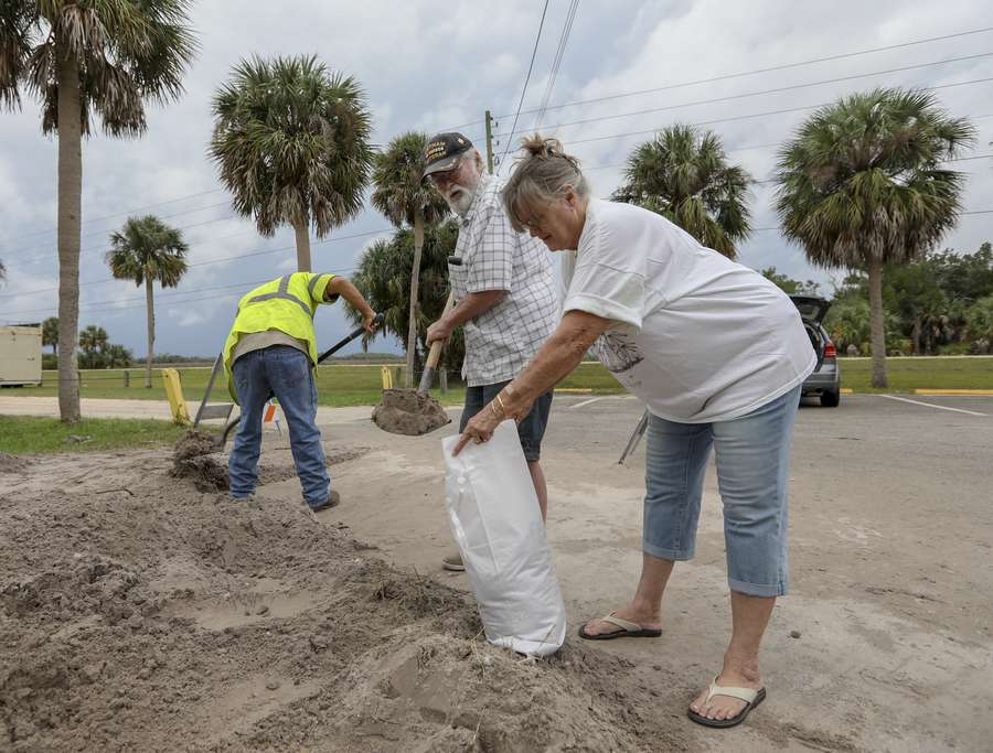 Doug Hodgins, left, along with his wife Linda, of Panama City load sand in bags at Linda Pedersen Preserve Wednesday, Oct. 10, 2018 in Weeki Wachee. The couple live on a boat in Panama City and were forced to leave as Hurricane Michael barreled toward the coast. The Hodgins are staying at Doug's brother's home but fear a high tide may later this afternoon may flood the home. [CHRIS URSO | Times]