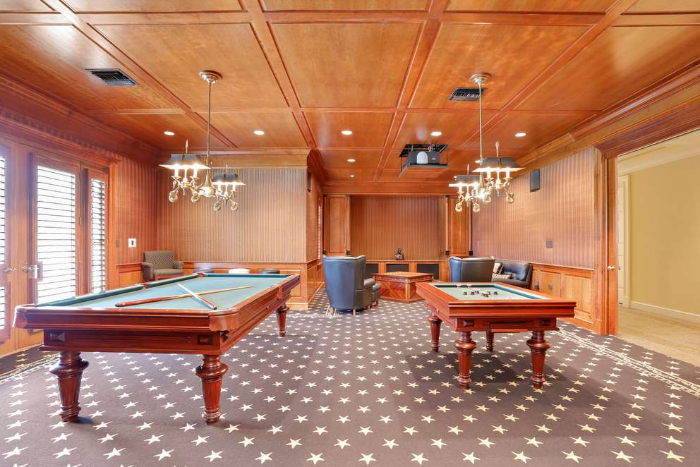 The home includes a gym, game room and a four-car garage plus golf cart. [Courtesy of Tony Sica Photography]