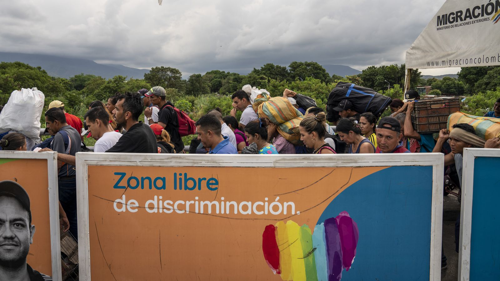 Crowds jostle through the line to re-enter Venezuela at the border crossing, many carrying heavy packs on their shoulders with goods purchased in Colombia. Many Venezuelans cross the border to buy what they need in Colombia.