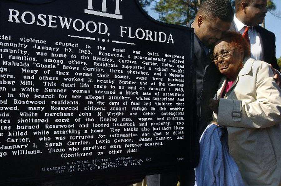 In 2004, Rosewood survivor Robie Mortin came to see Florida Gov. Jeb Bush dedicate a highway sign to the victims of the Rosewood massacre. The marker sits at the end of Fuji Scoggins' driveway, on the only road to Cedar Key. [Times (2004)]