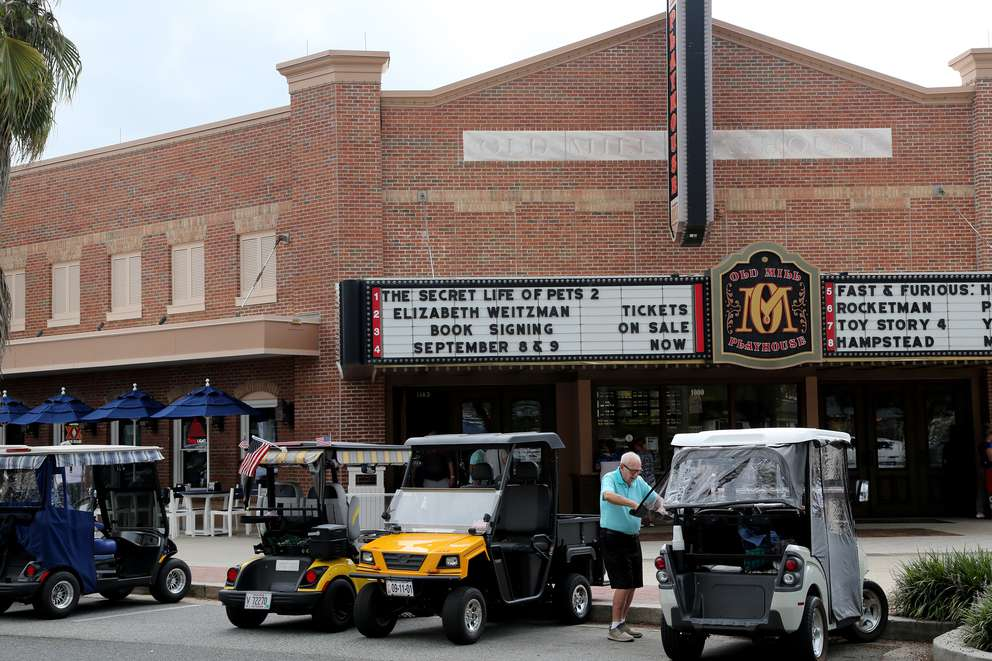 Frank Lame, 89, rolls up an enclosure on his golf cart while parked outside the Old Mill Playhouse (movie theater) on Monday at The Villages in Sumter County. [DOUGLAS R. CLIFFORD | Times]