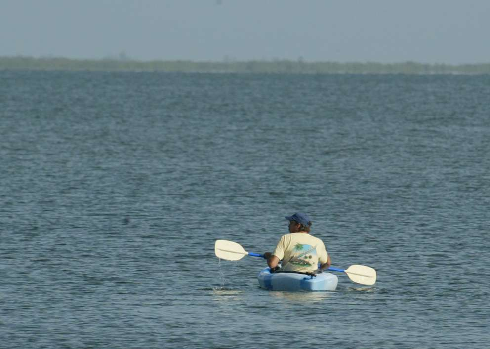 A kayaker paddles around the cloudy green-blue waters of Blackwater Sound in Key Largo. (AP Photo/Wilfredo Lee)