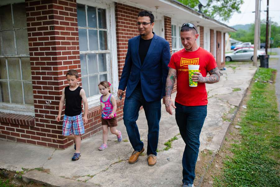 Heval Mohamed Kelli walks with Chris Buckley and his children, C.J., 6, and Miera, 3, outside their home in LaFayette, Georgia, about two hours northwest of Atlanta. [Photo for The Washington Post by Kevin D. Liles]
