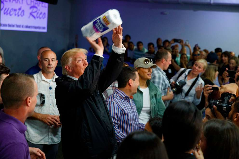 President Donald Trump President Donald Trump tosses paper towels into a crowd as he hands out supplies at Calvary Chapel, Tuesday, Oct. 3, 2017, in Guaynabo, Puerto Rico. Trump is in Puerto Rico to survey hurricane damage. (Associated Press)