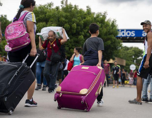 La gente que viene de Venezuela rueda maletas y bolsos hacia la frontera colombiana el sábado 7 de diciembre de 2019, en Cúcuta.