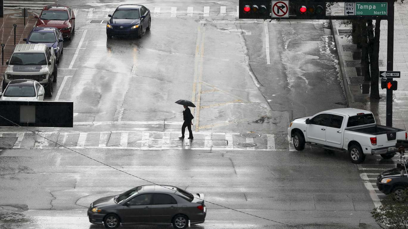 CHRIS URSO   Times An unidentified pedestrian crosses Whiting Street at the intersection of Tampa Street while carrying an umbrella Wednesday, May 30, 2018 in Tampa. Rain continued to fall on the Tampa Bay region Wednesday. Rain chances will stay near 60 percent with afternoon highs in the lower 80s, forecasters said.