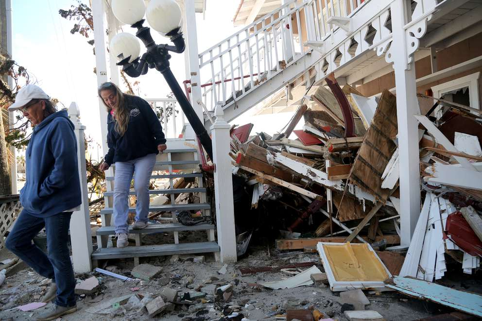 Amy Hay, left, an employee of the Driftwood Inn, and Shawna Wood explore the remains of the property in December. DOUGLAS R. CLIFFORD | Times