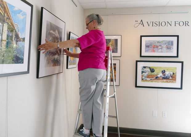 Jo Baughman, director of the Pasco Fine Arts Council, arranges artwork for an upcoming exhibit, 'Moments in Time.' The exhibit features the artwork of Suzanne Natzke, and will be held through Oct. 21 at the council's new gallery at Avalon Park West in Wesley Chapel.