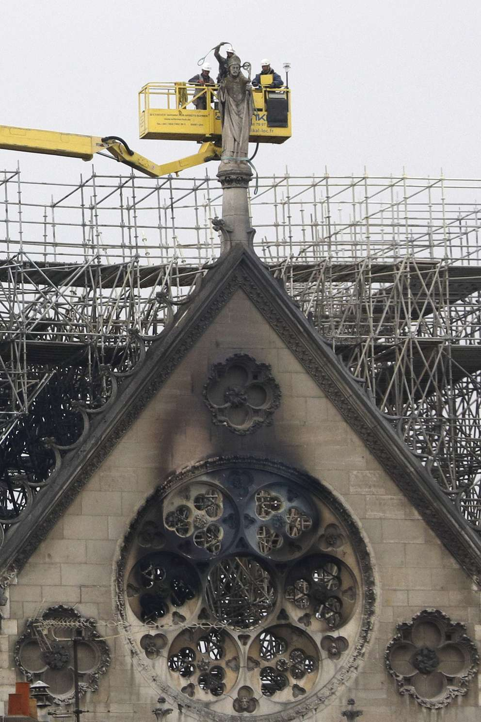 Experts prepare to lift a statue from the damaged Notre Dame cathedral after the fire in Paris, Tuesday, April 16, 2019. Experts are assessing the blackened shell of Paris' iconic Notre Dame cathedral to establish next steps to save what remains after a devastating fire destroyed much of the almost 900-year-old building. With the fire that broke out Monday evening and quickly consumed the cathedral now under control, attention is turning to ensuring the structural integrity of the remaining building. (AP Photo/Kamil Zihnioglu)