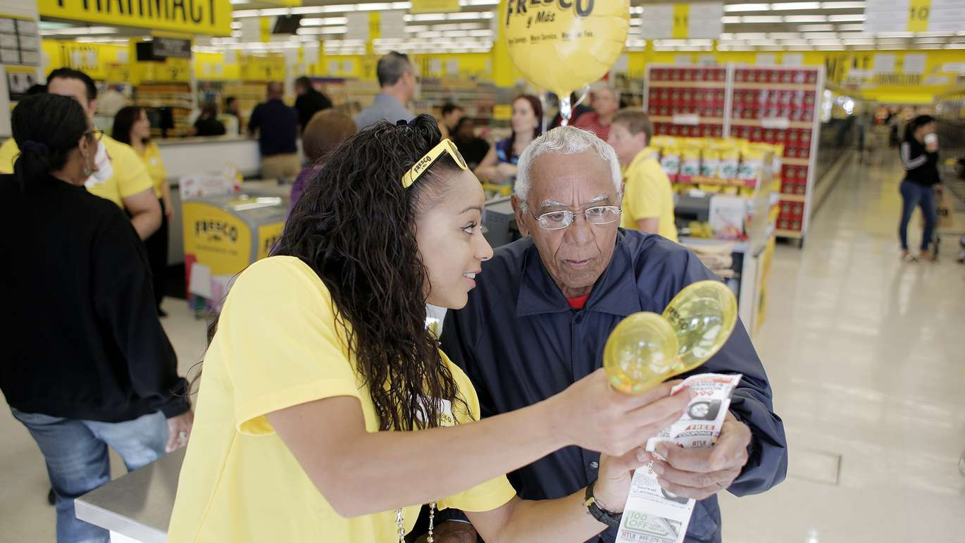 Frescos Y Mas associate Solimar Linares, 30, left, helps Andres Castro, 77, of Tampa with items on his receipt during the grand opening of the new grocery store. [OCTAVIO JONES | Times]