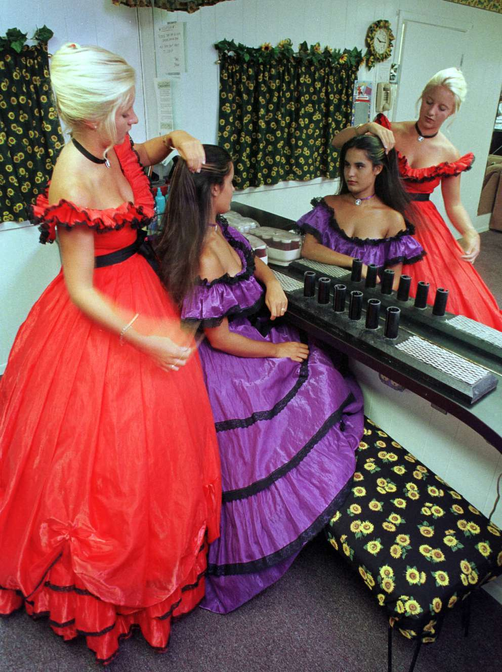Cypress Gardens Belles Katie Campbell, in red, and Lisa Torres get ready for duty in their distinctive costumes. Times (1999)