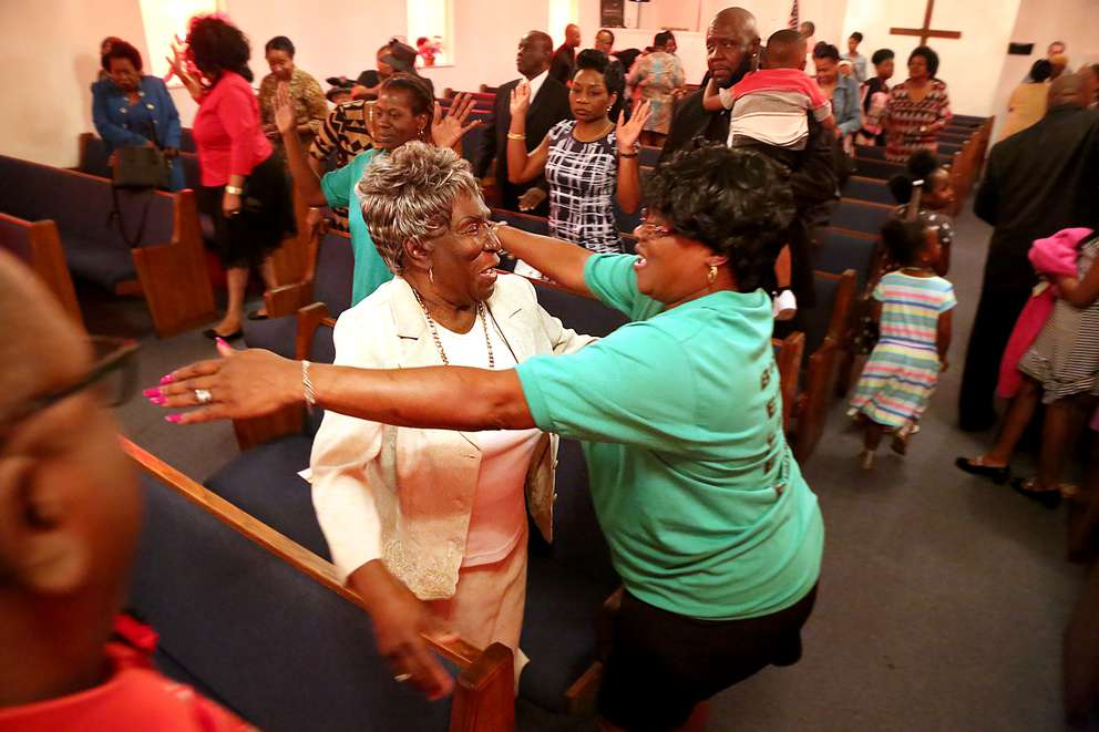 Eunice Collins, left, and Mary Ann Johnson greet each other on a Sunday at Mt. Olive.
