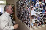 James T. Reynolds Sr. looks at a bulletin board covered in photos of cancer patients he says received assistance from Cancer Fund of America. Over the past decade, the charity has received nearly $100 million, but only 2 percent of that has gone to directly help cancer patients.